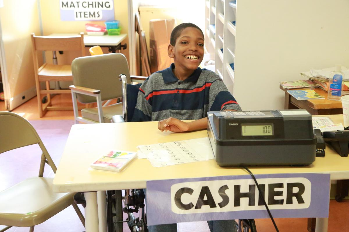 student smiling while learning how to work the cash register