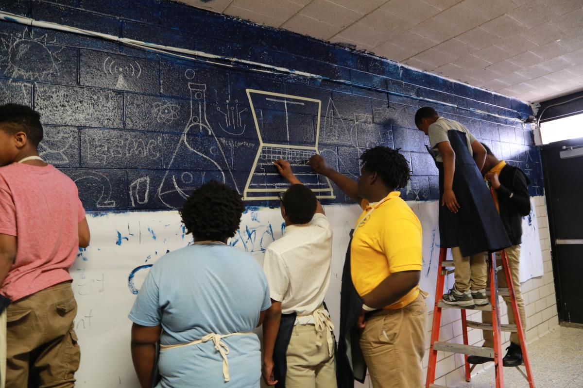 Students working on a mural in the hallway of there school