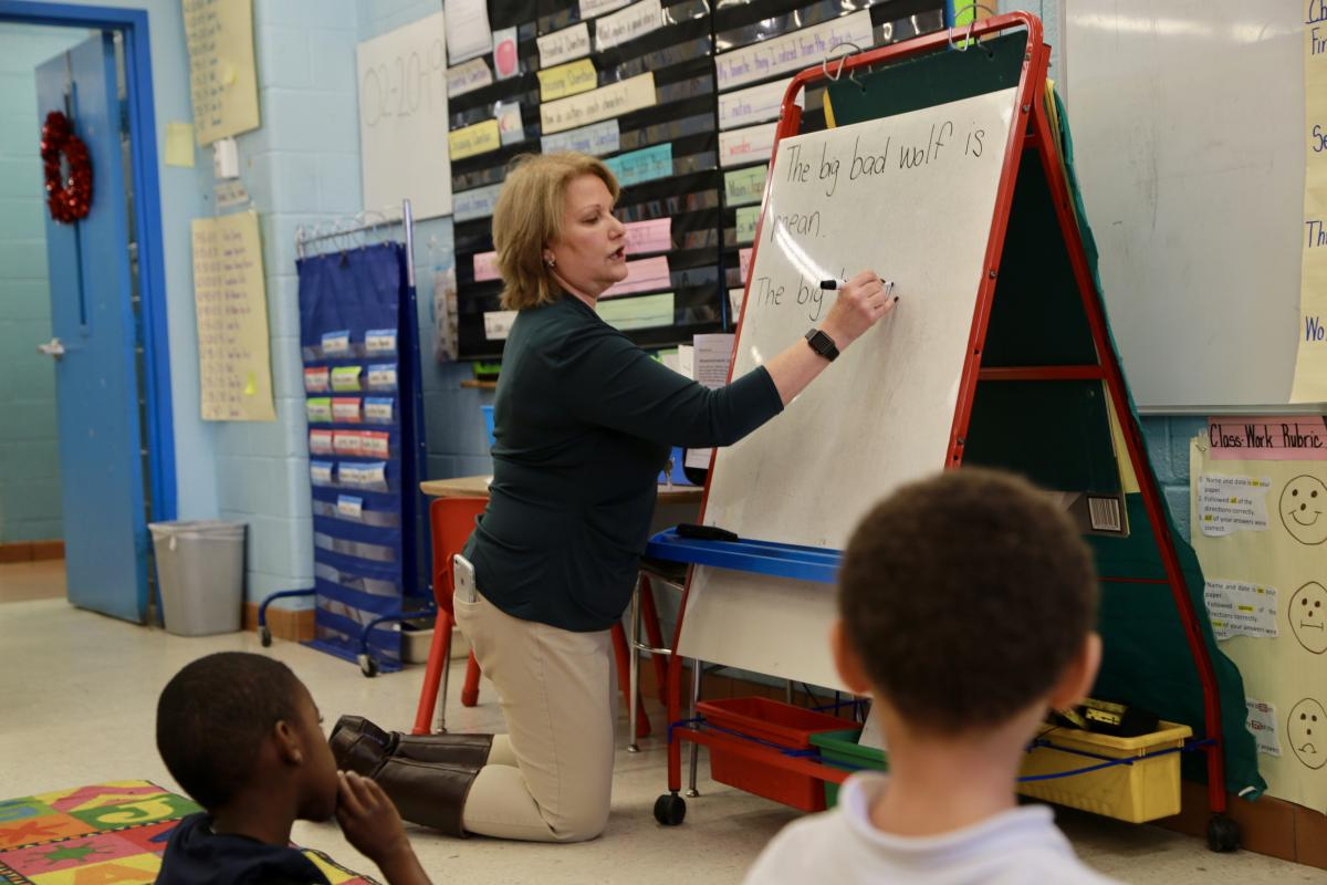 teacher writing on the board in a classroom