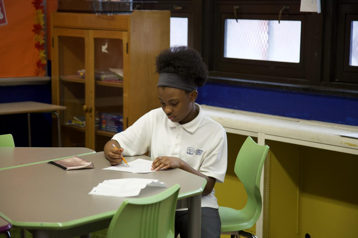 student writing at her desk