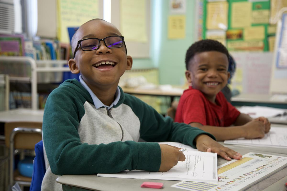 students smiling at their desk