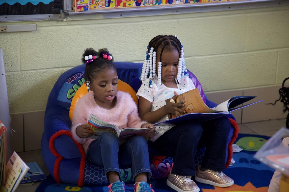 two students sitting and reading their books.