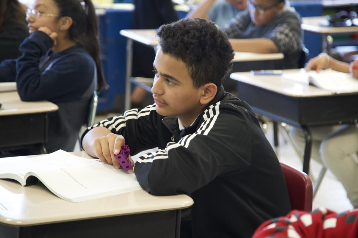 student listening to his teacher explain the instructions to their classwork