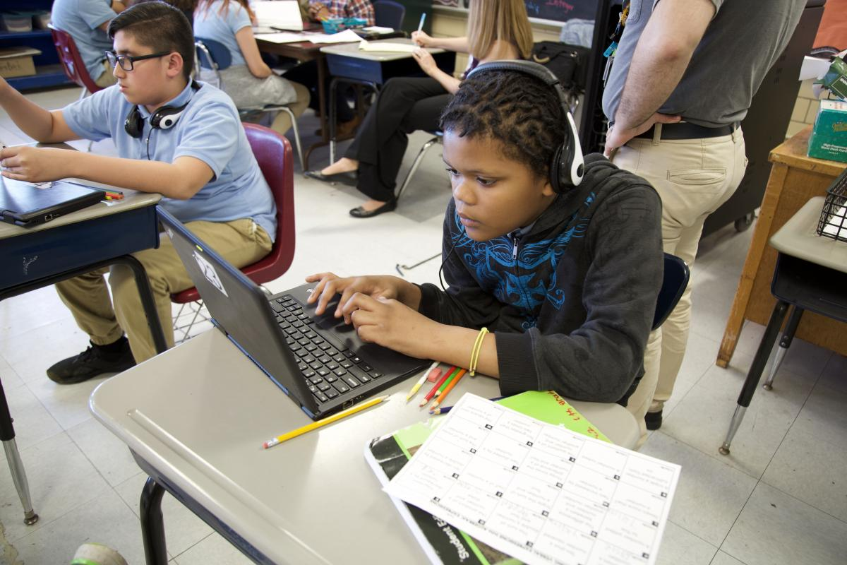 student sitting at his desk working on the computer