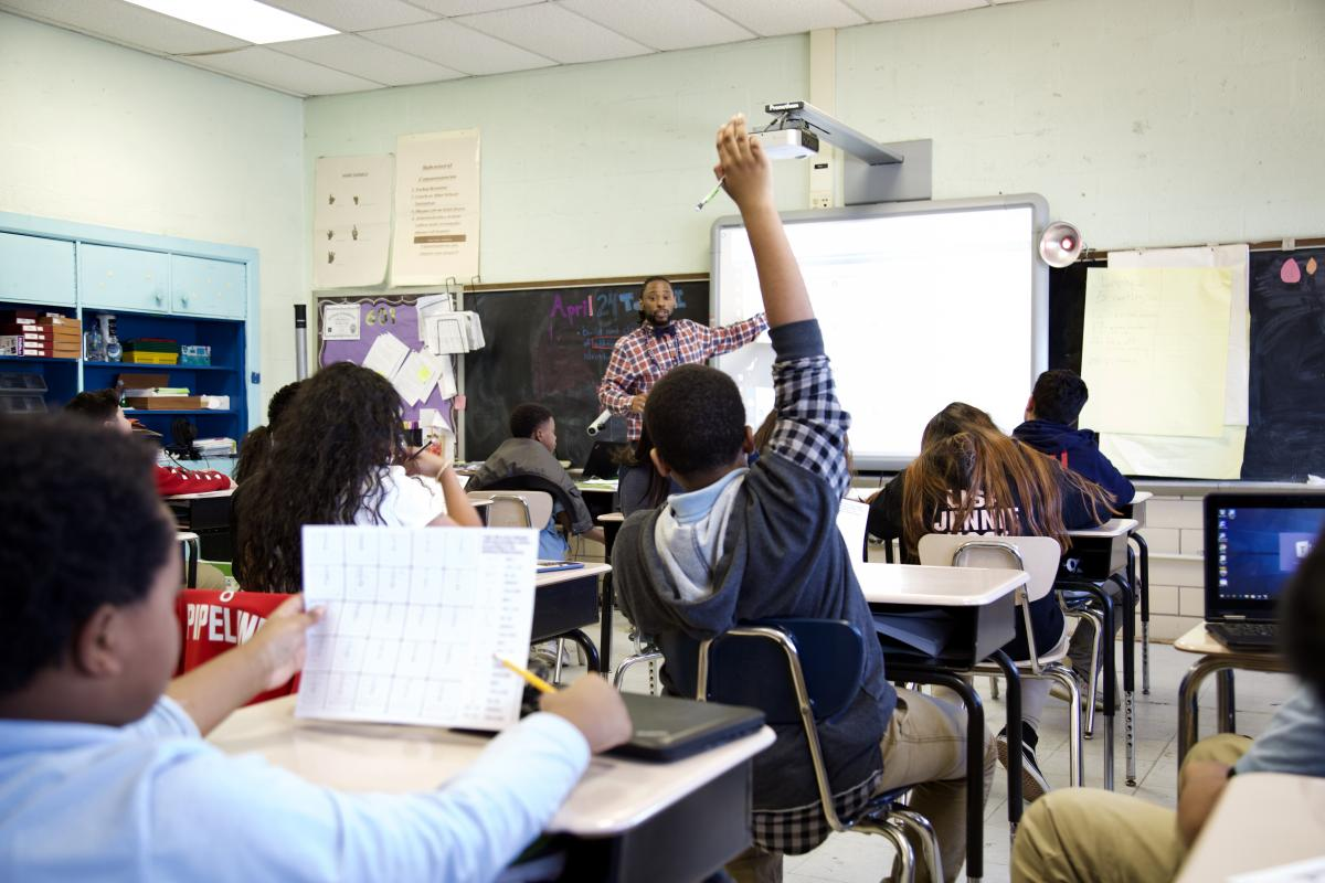 student raising his hand to answer the teachers question in math class